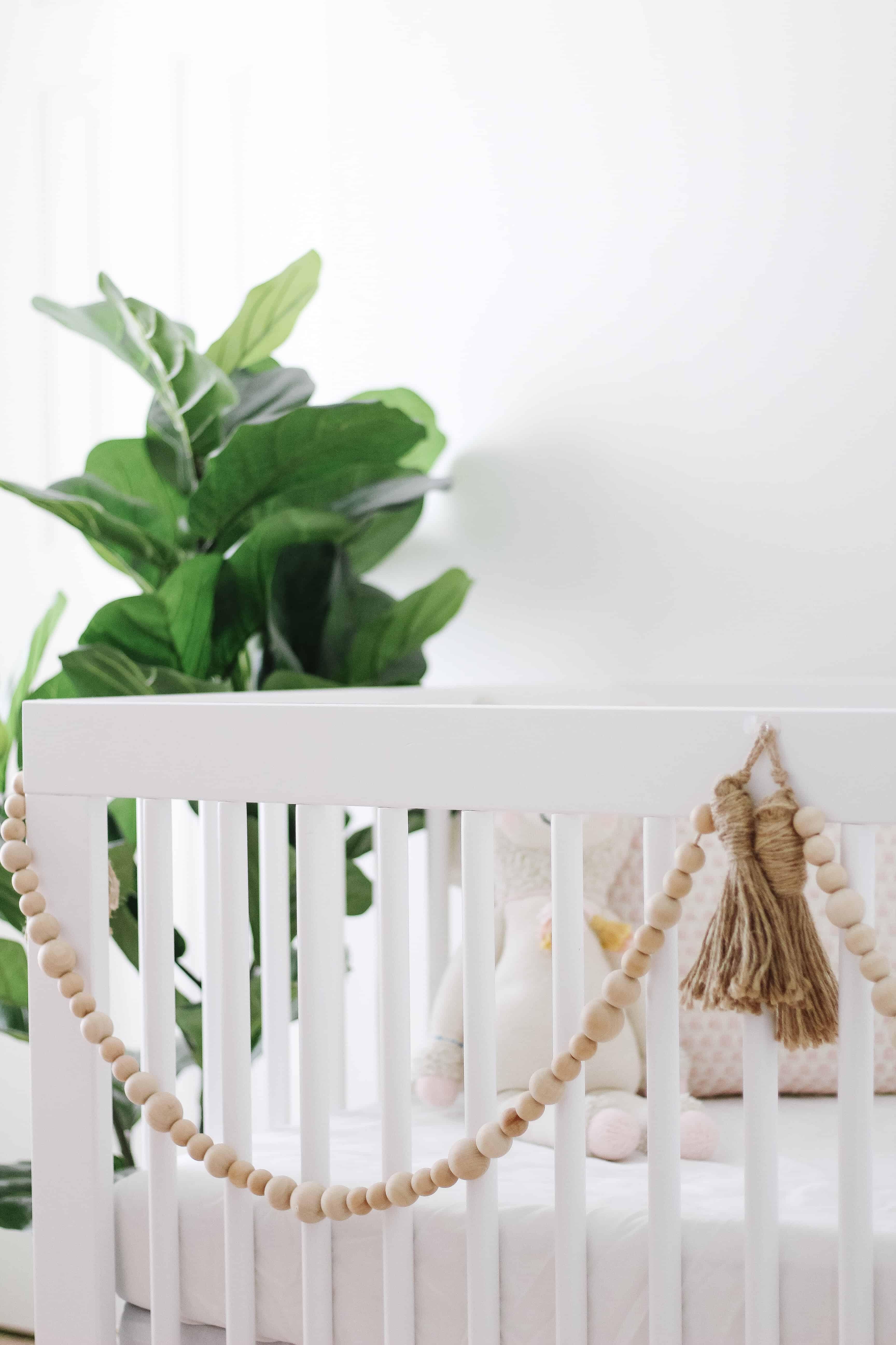 white crib with wood beads