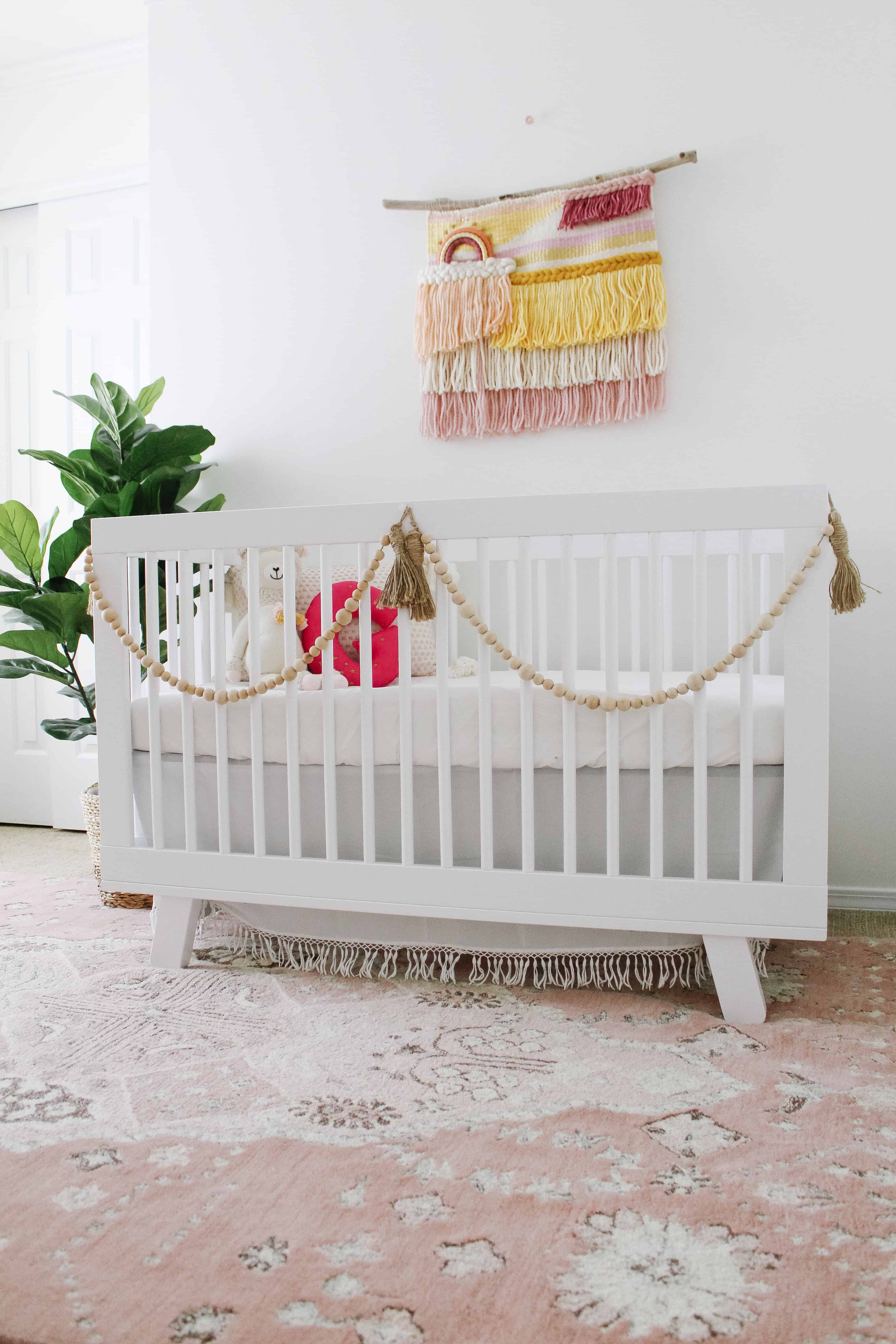 White crib with pink boho accents