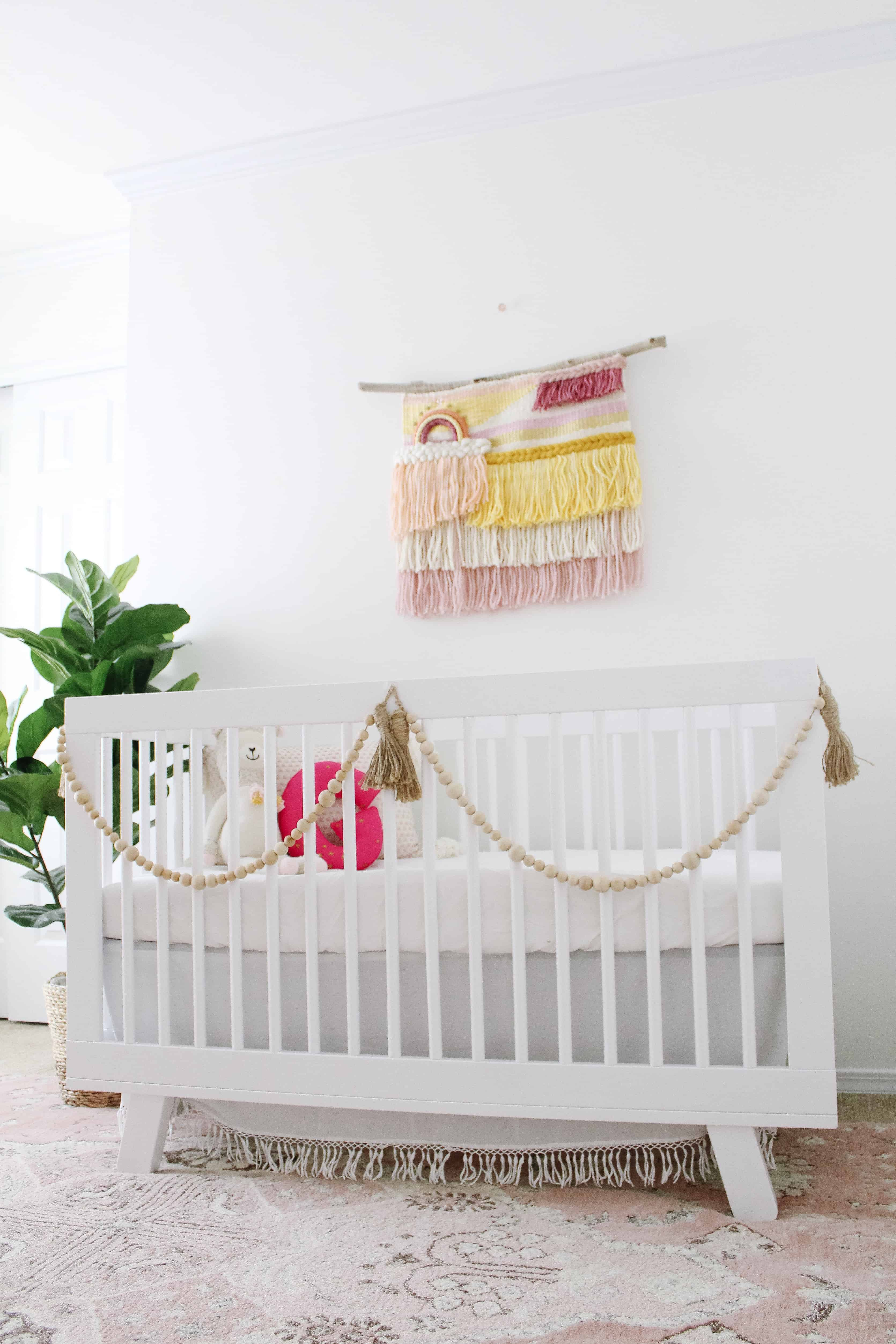 White crib with macrame hanging over