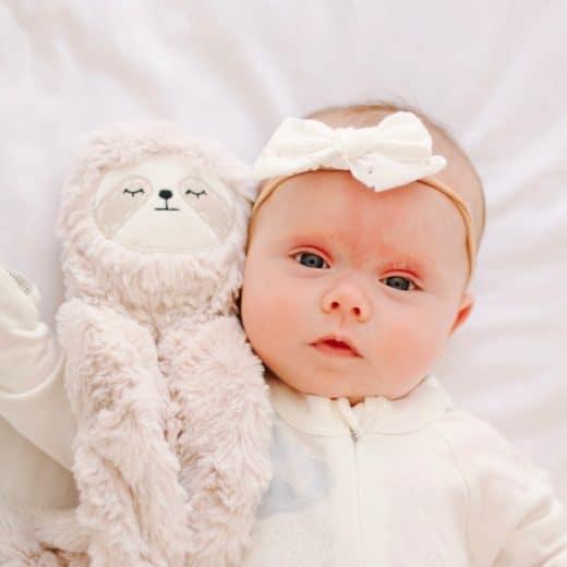 baby girl with slumberkins sloth