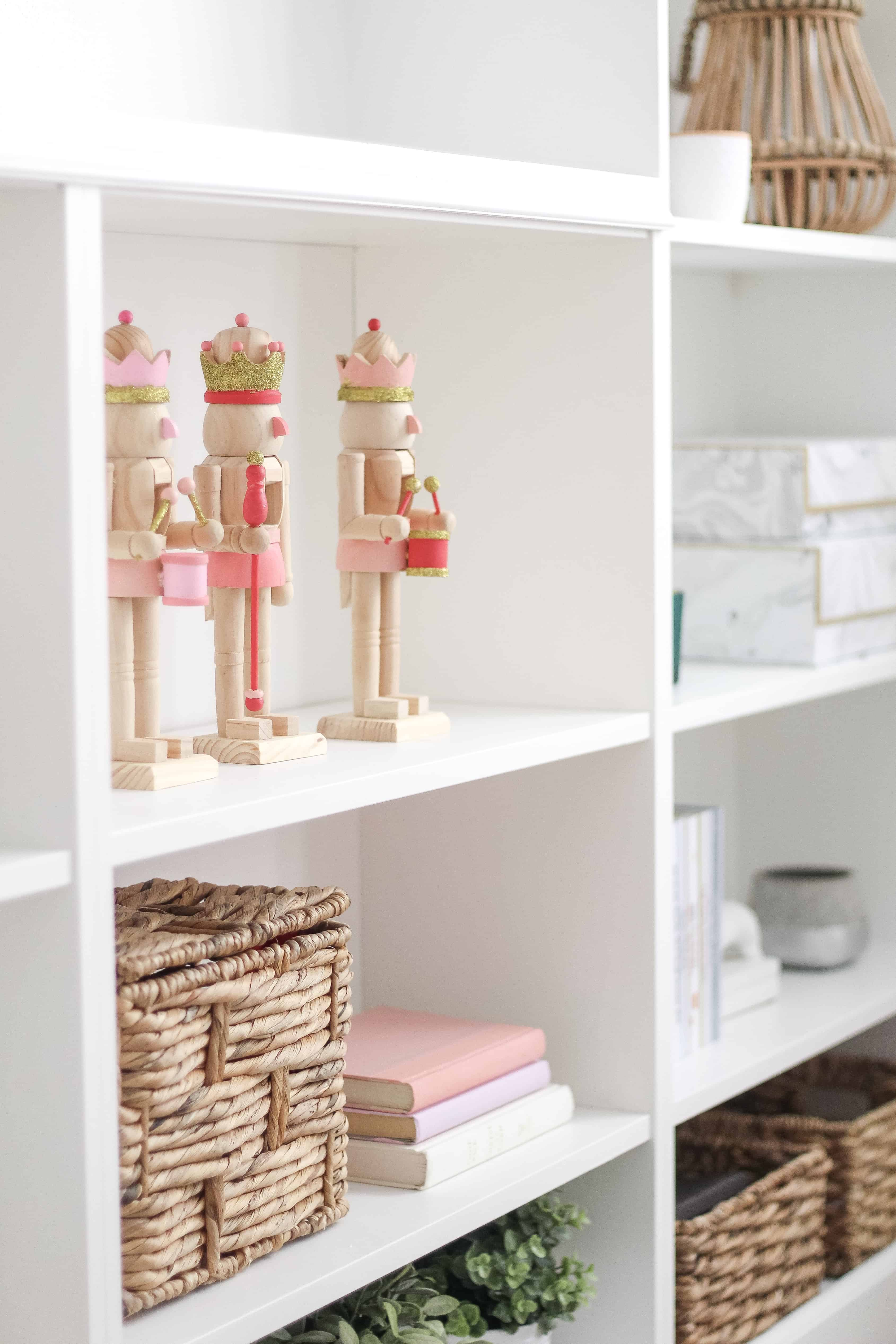 pink and gold wood nutcrackers on built in shelving