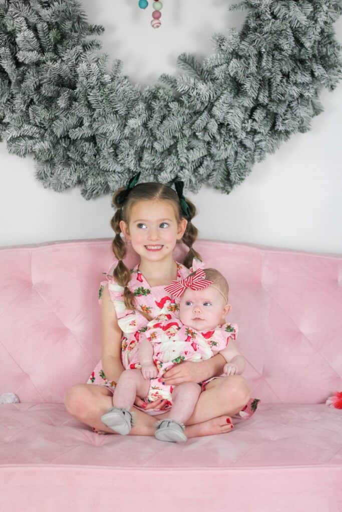sisters on pink couch in pink Santa dresses