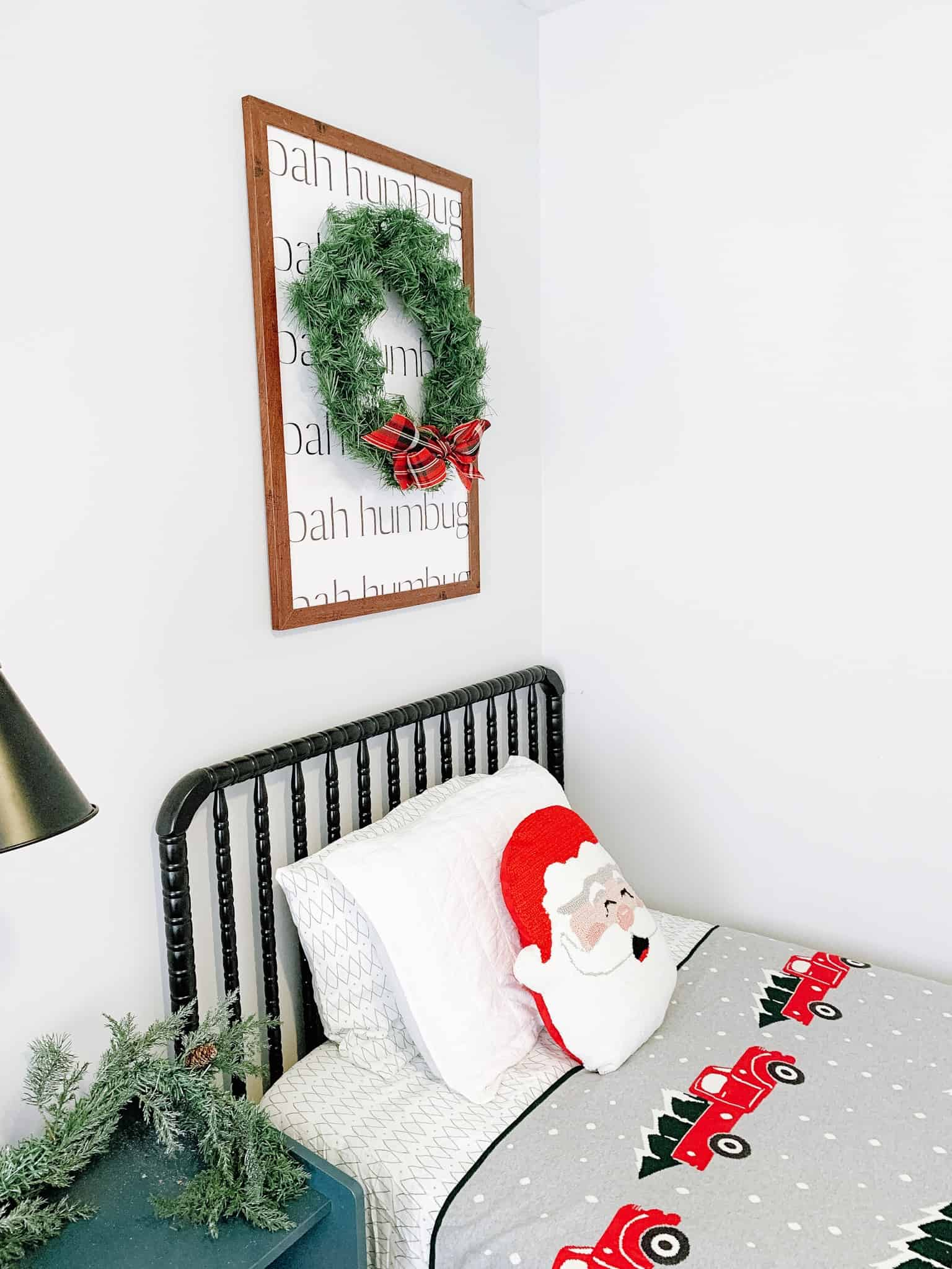 Boys bed with wreath over it and Santa pillow for Christmas