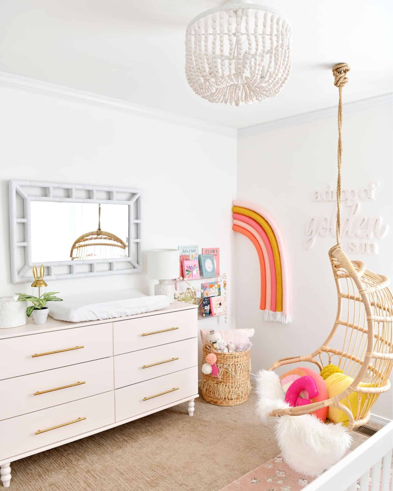 baby girl nursery with hanging chair and rainbow
