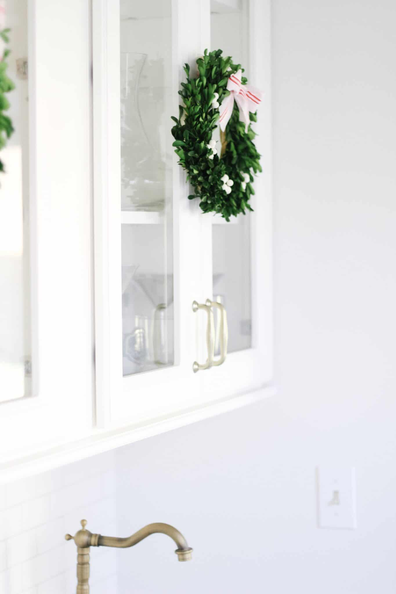 Boxwood Wreaths on white cabinets