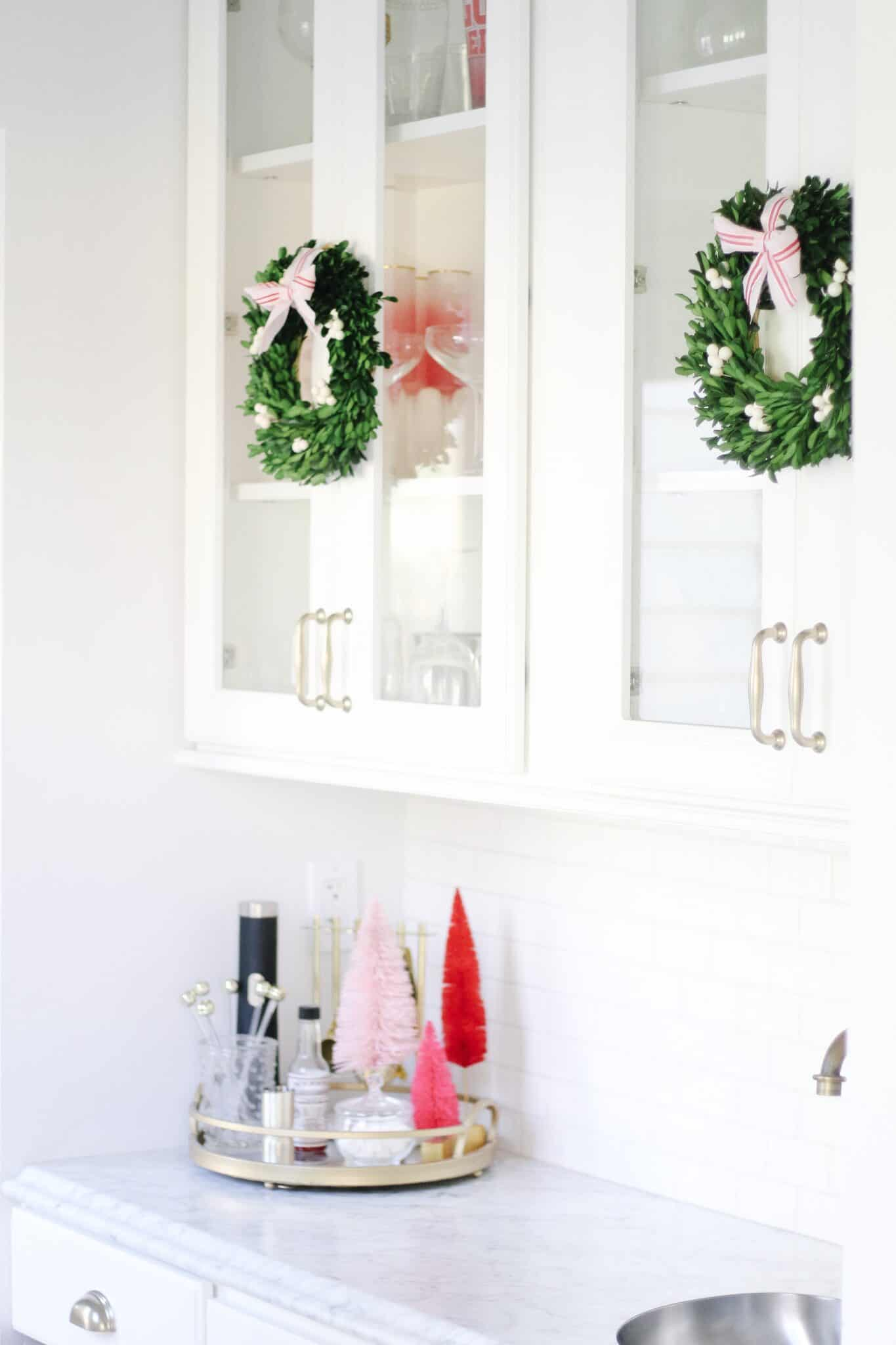 Boxwood wreaths on white kitchen cabinets