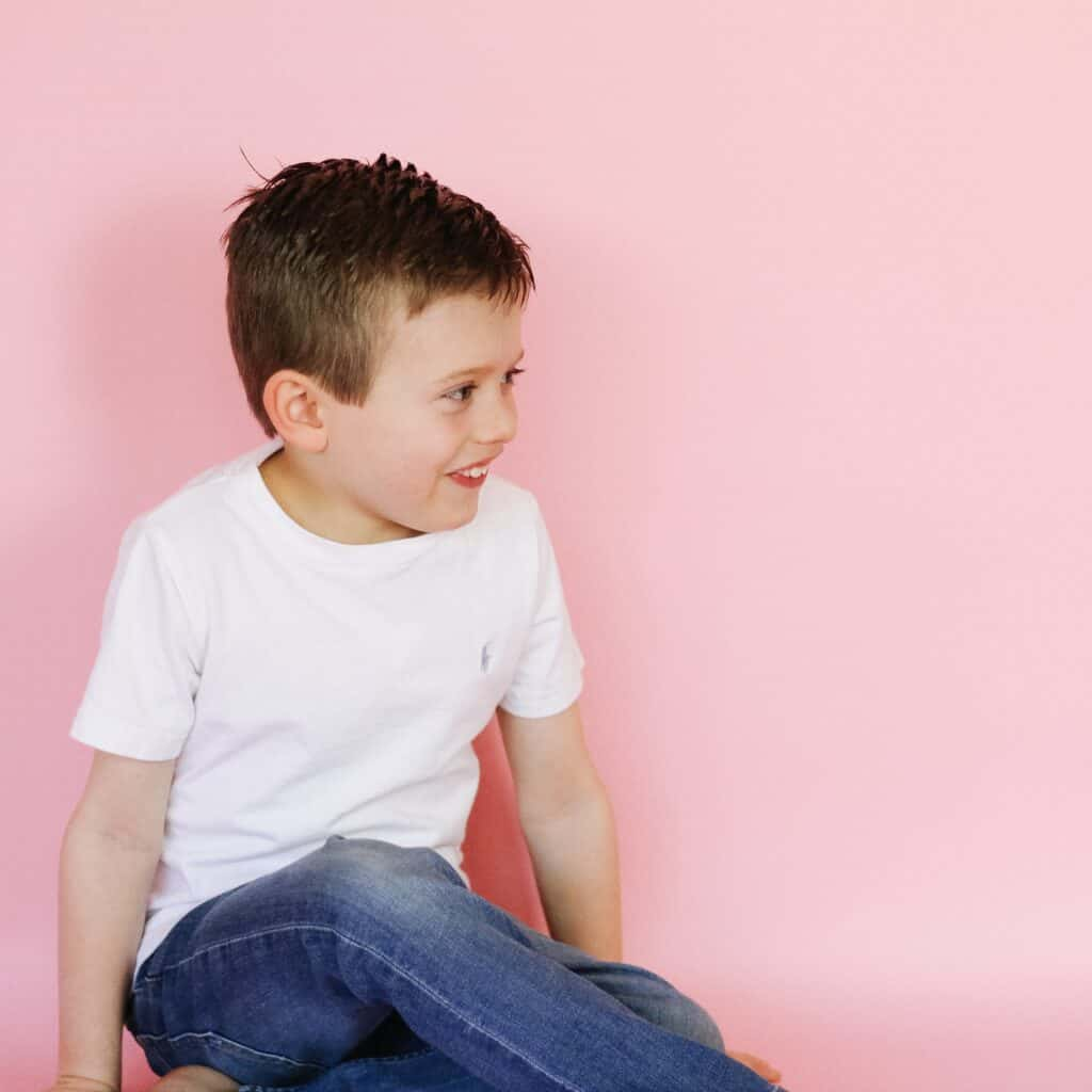 little boy in white against pink backdrop
