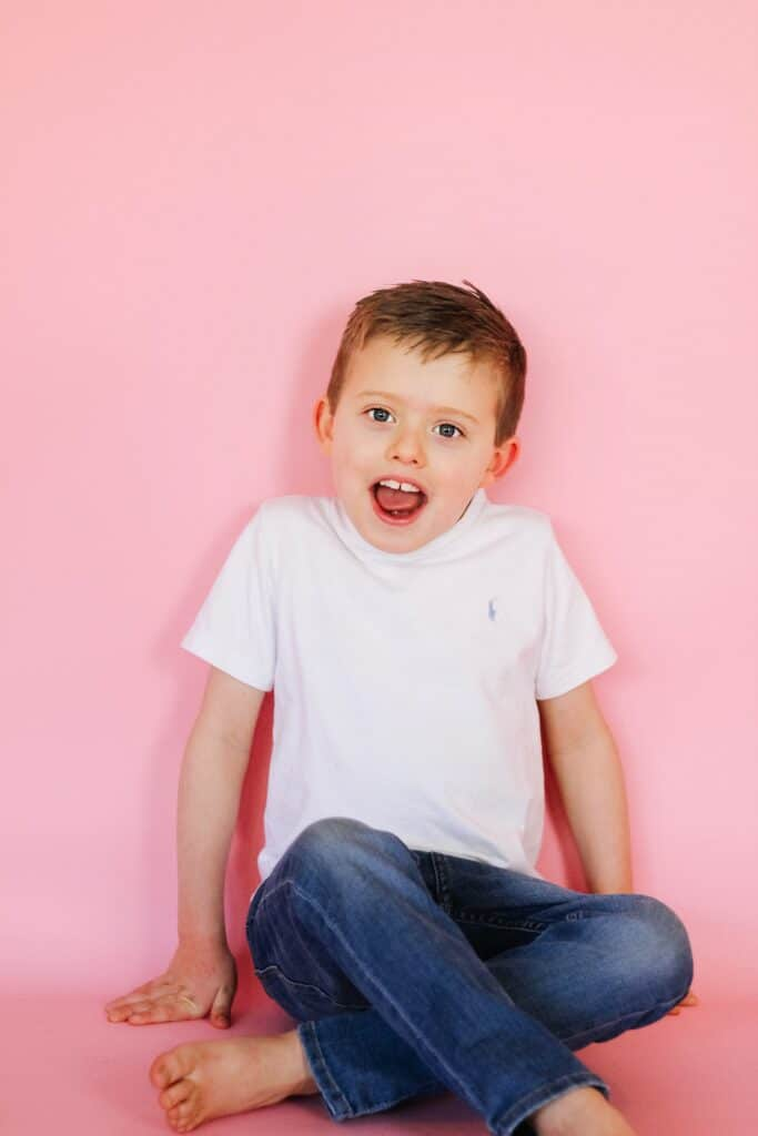 little boy against pink backdrop