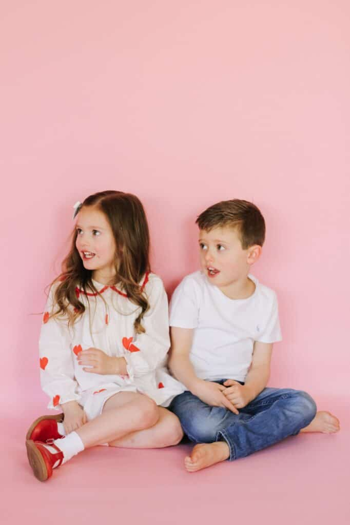 Toddlers dressed for valentines day  against pink backdrop