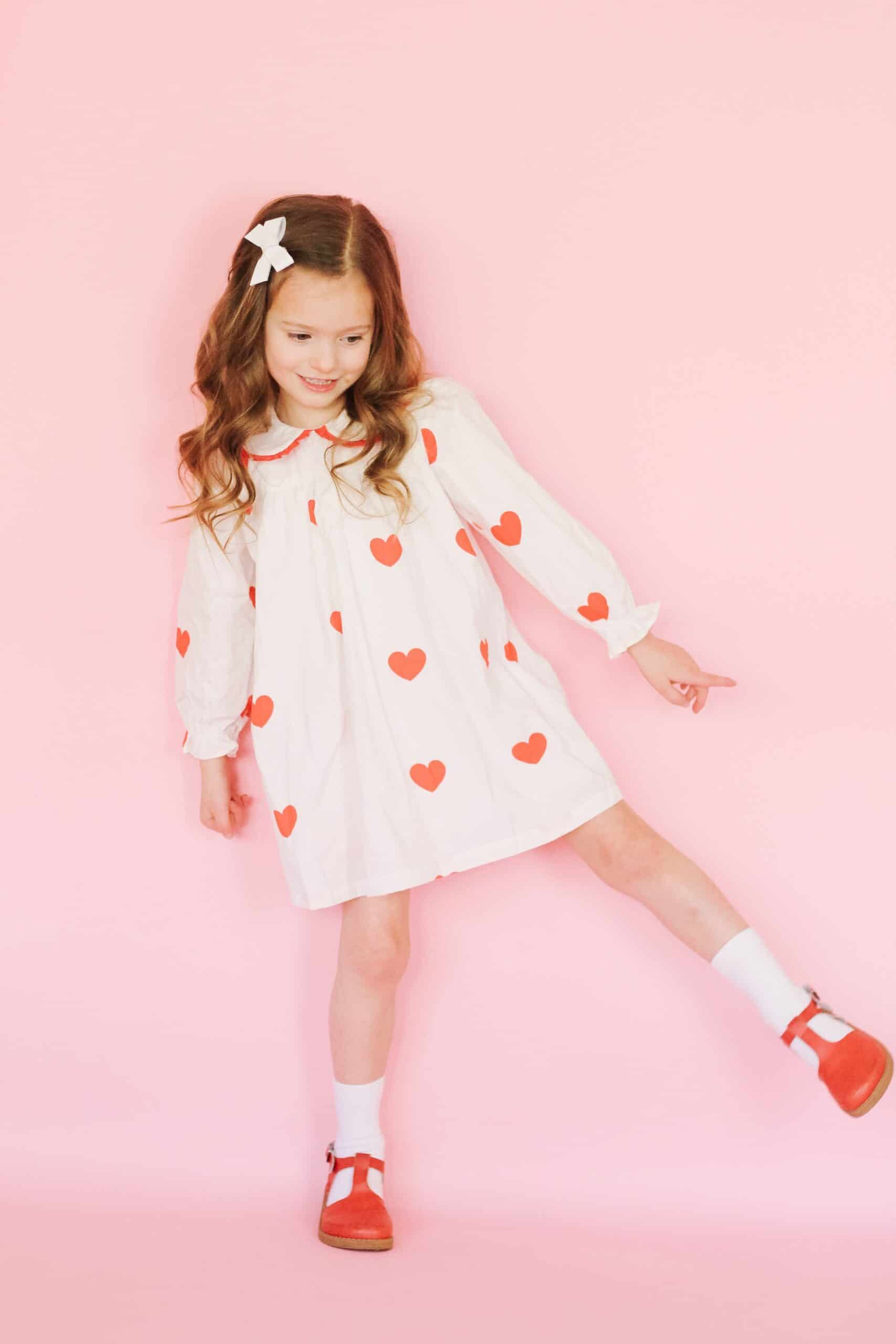 Toddler girl in white heart dress and red freshly picked Mary Janes