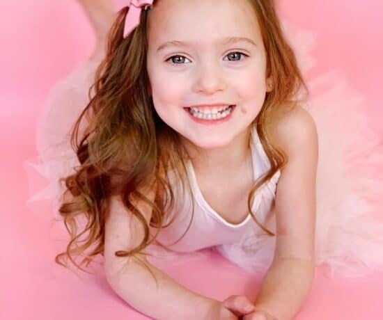Toddler girl in white plum tutu on pink backdrop