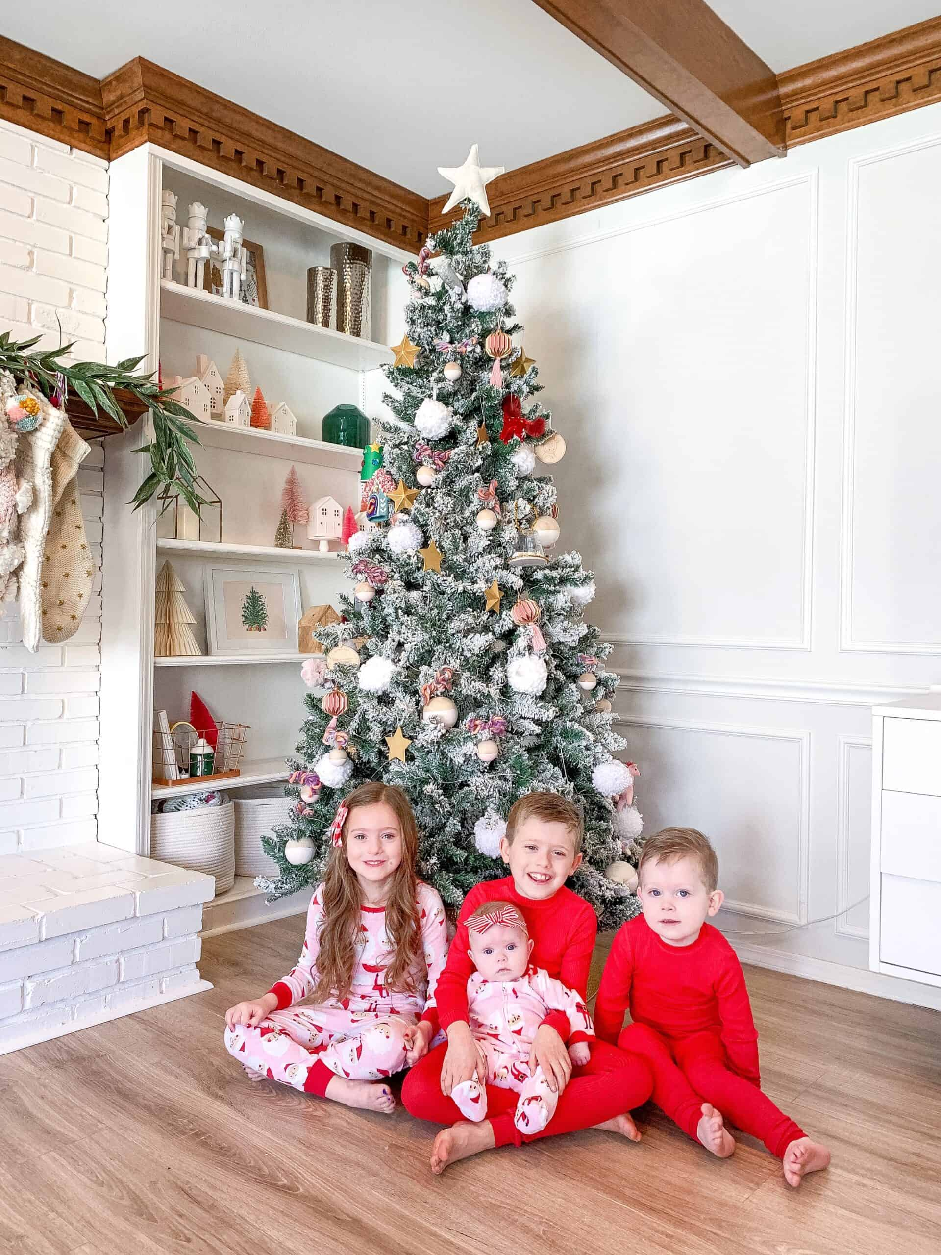 Kids in pajamas in front of a Christmas Tree