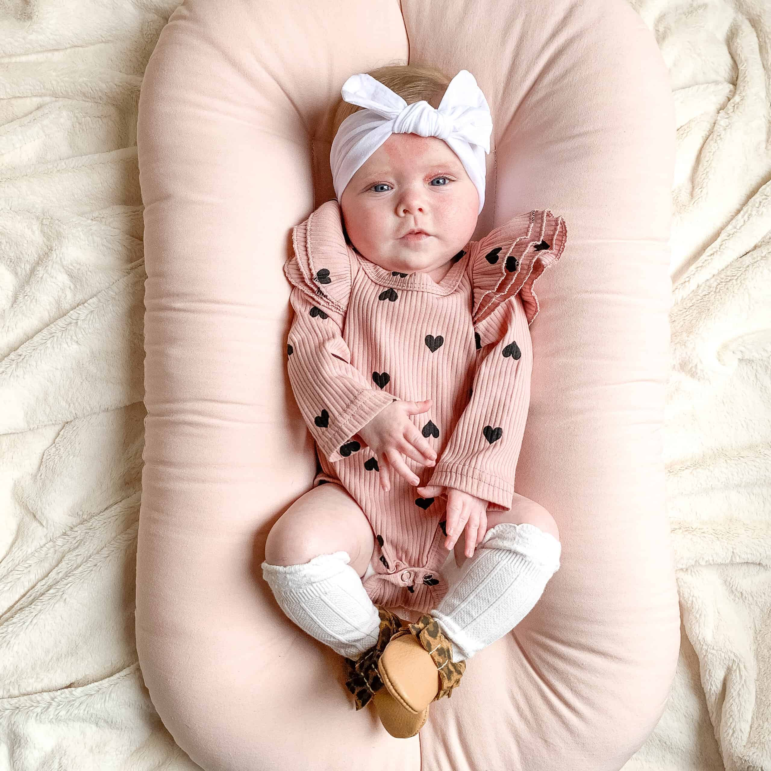 Baby girl on pink snuggle me organic