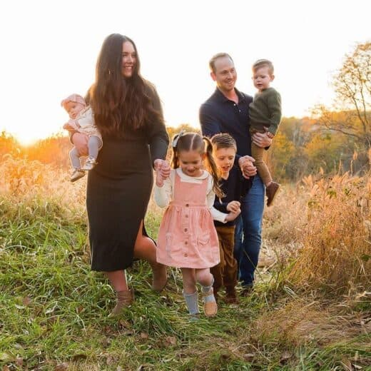 Family walking through field for family photos