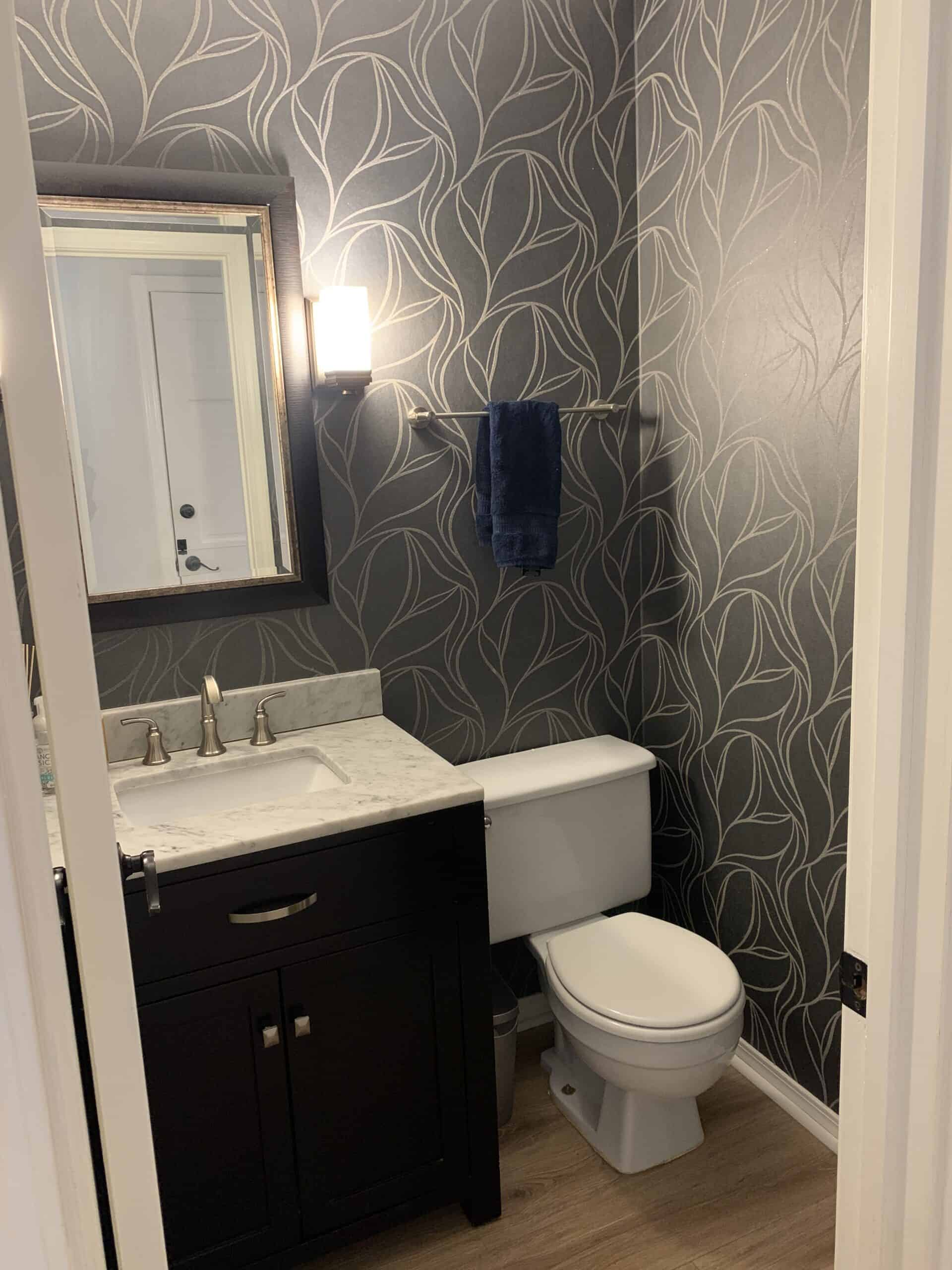 Powder room with navy blue and silver wallpaper