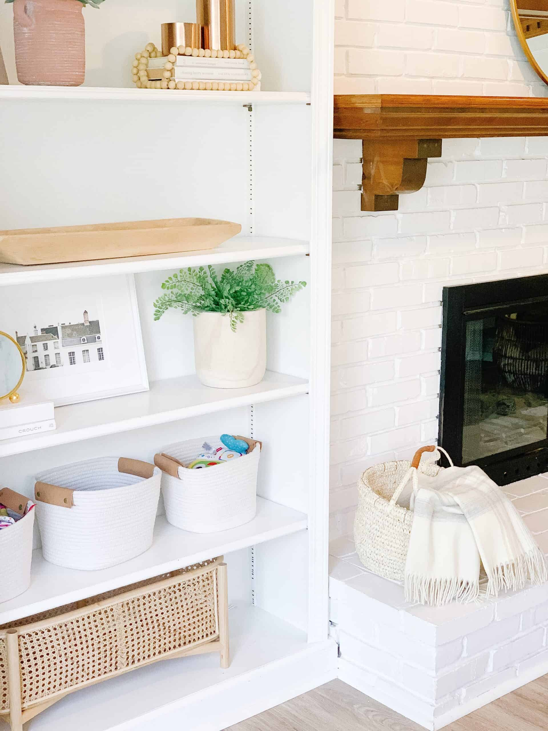 Organized built ins by white brick fireplace