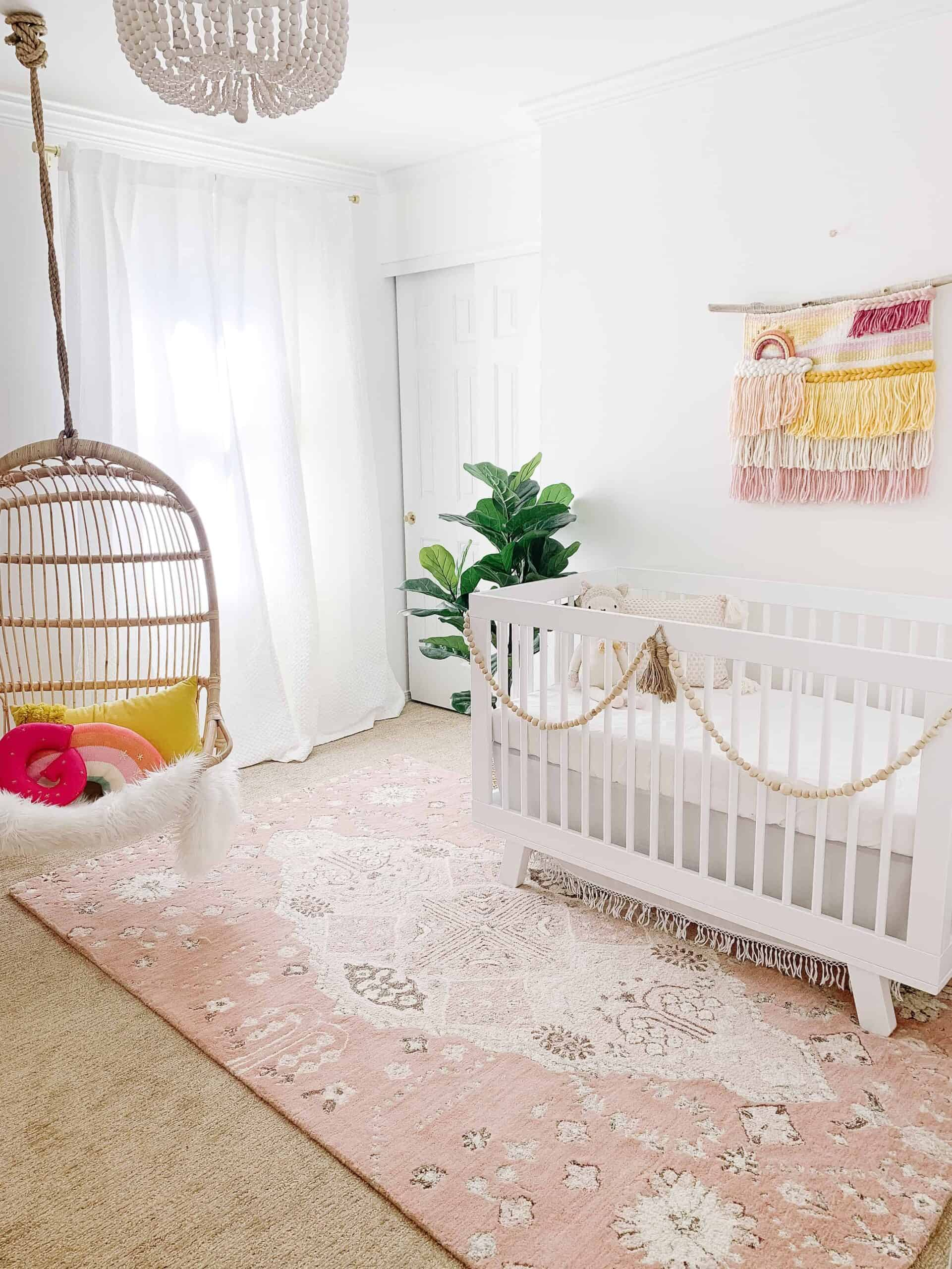 Boho pink nursery with hanging Serena and Lily Rattan Chair