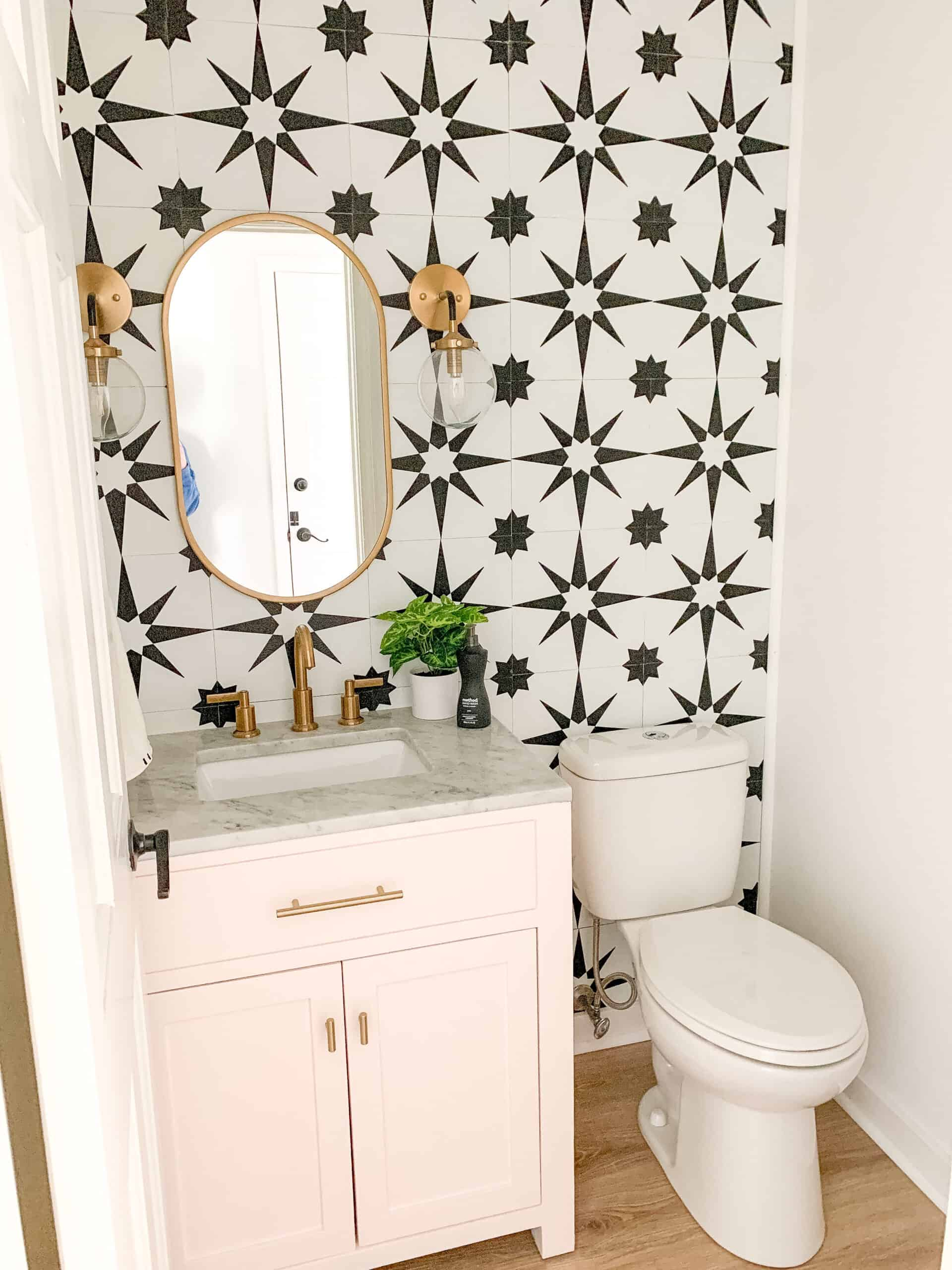 Blush pink powder room vanity with black and white tile wall