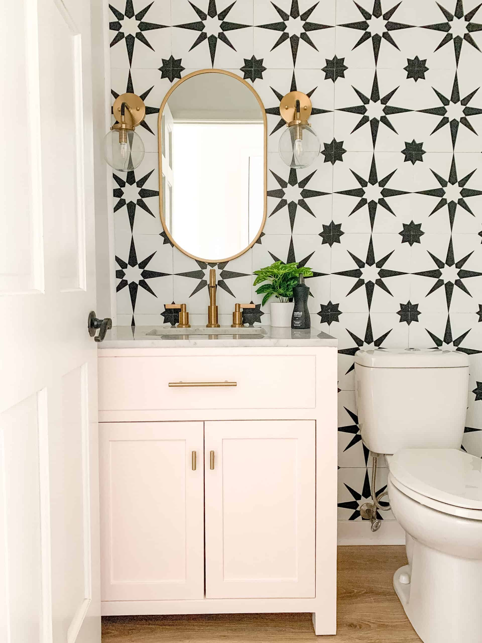 Bold pink powder room with black and white tile wall