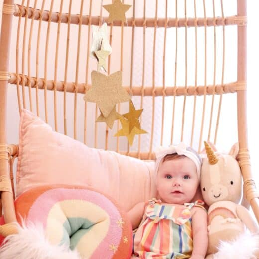 baby girl in hanging Serena and lily chair