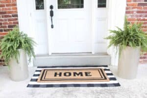 front porch with gold planters and layered doormats