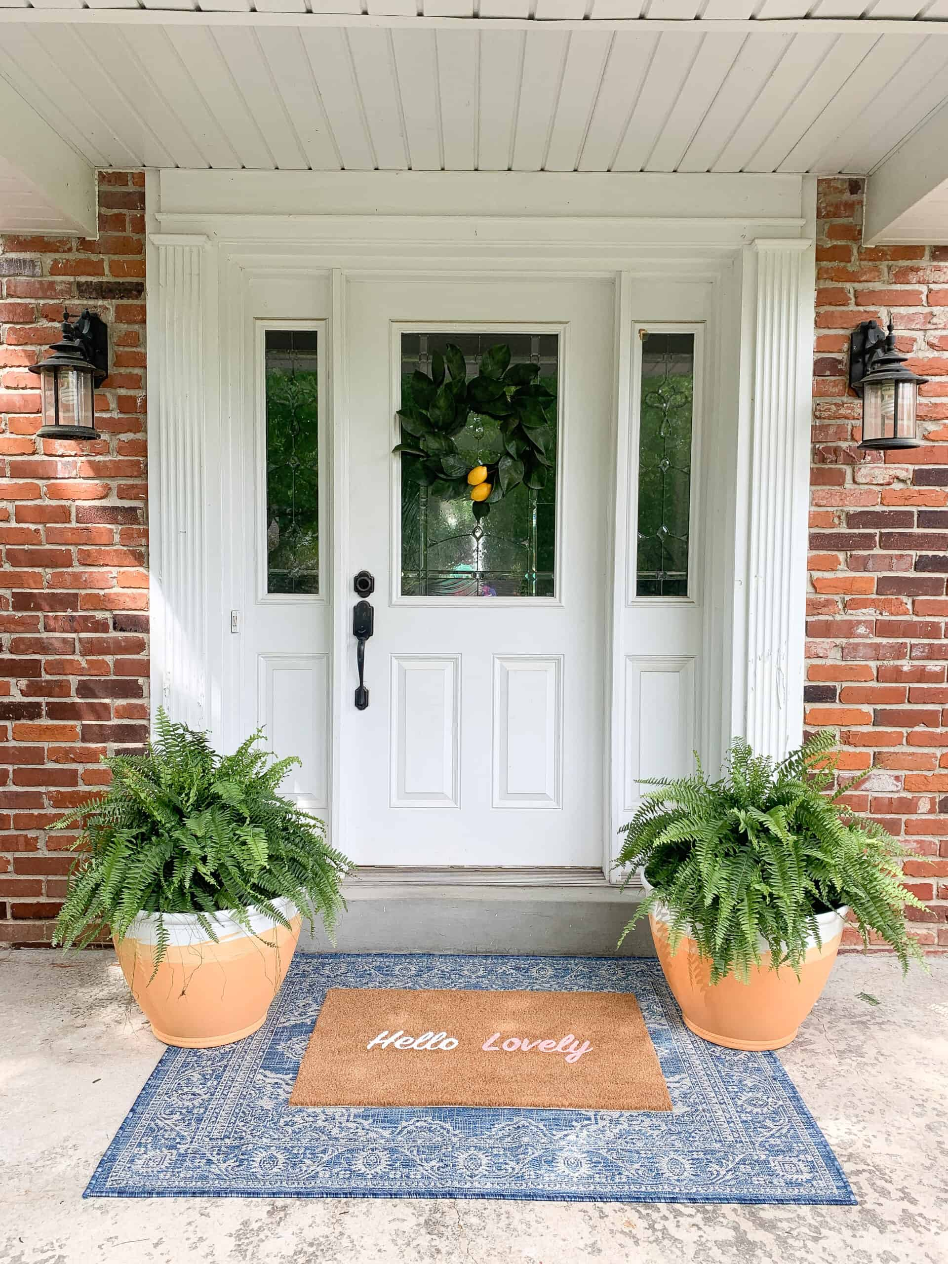 front porch with blue rug and terra-cotta planters