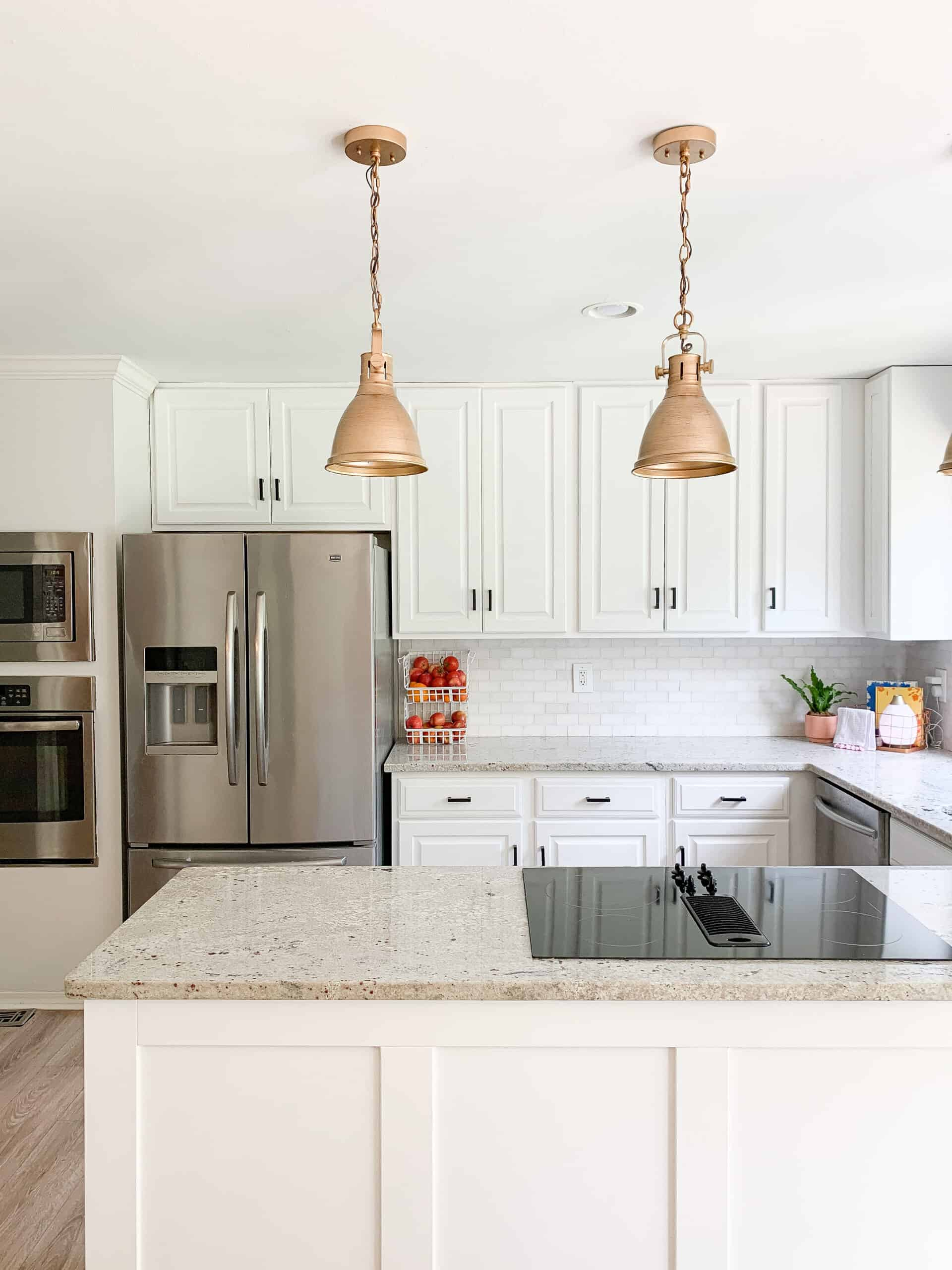 white kitchen cabinets with gold lights