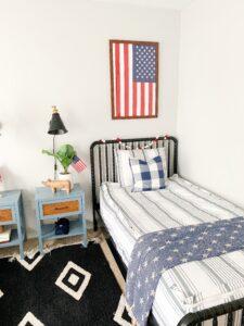 boys room with flag framed above bed