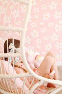 white hanging chair in front of Daisy wallpaper