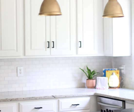 gold lights and black handles from amazon in white kitchen