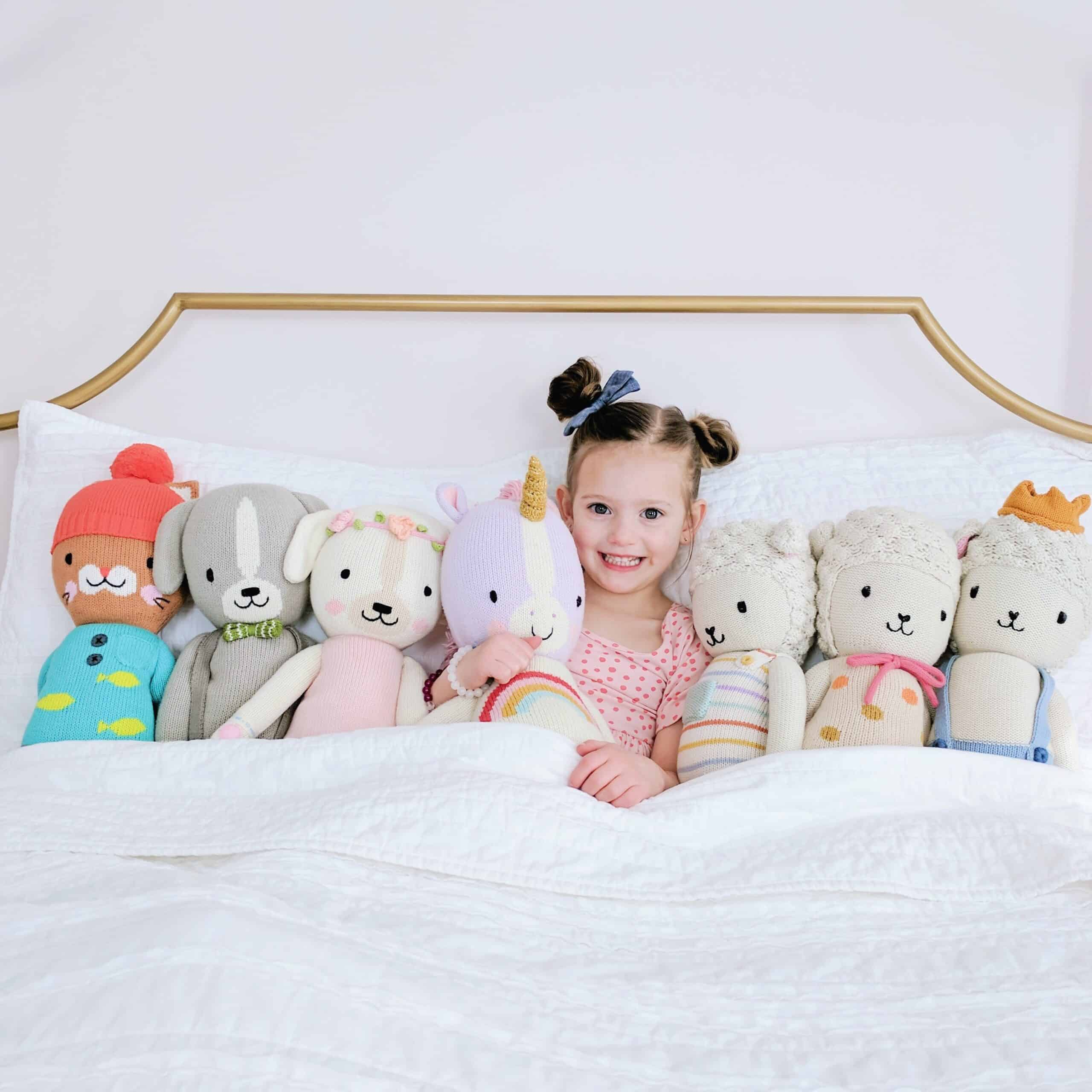little girl with cuddle and kind dolls