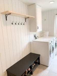 black bench in laundry room with mudroom