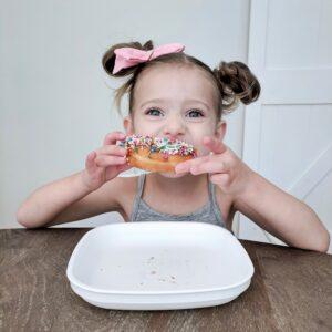 little girl eating a donut