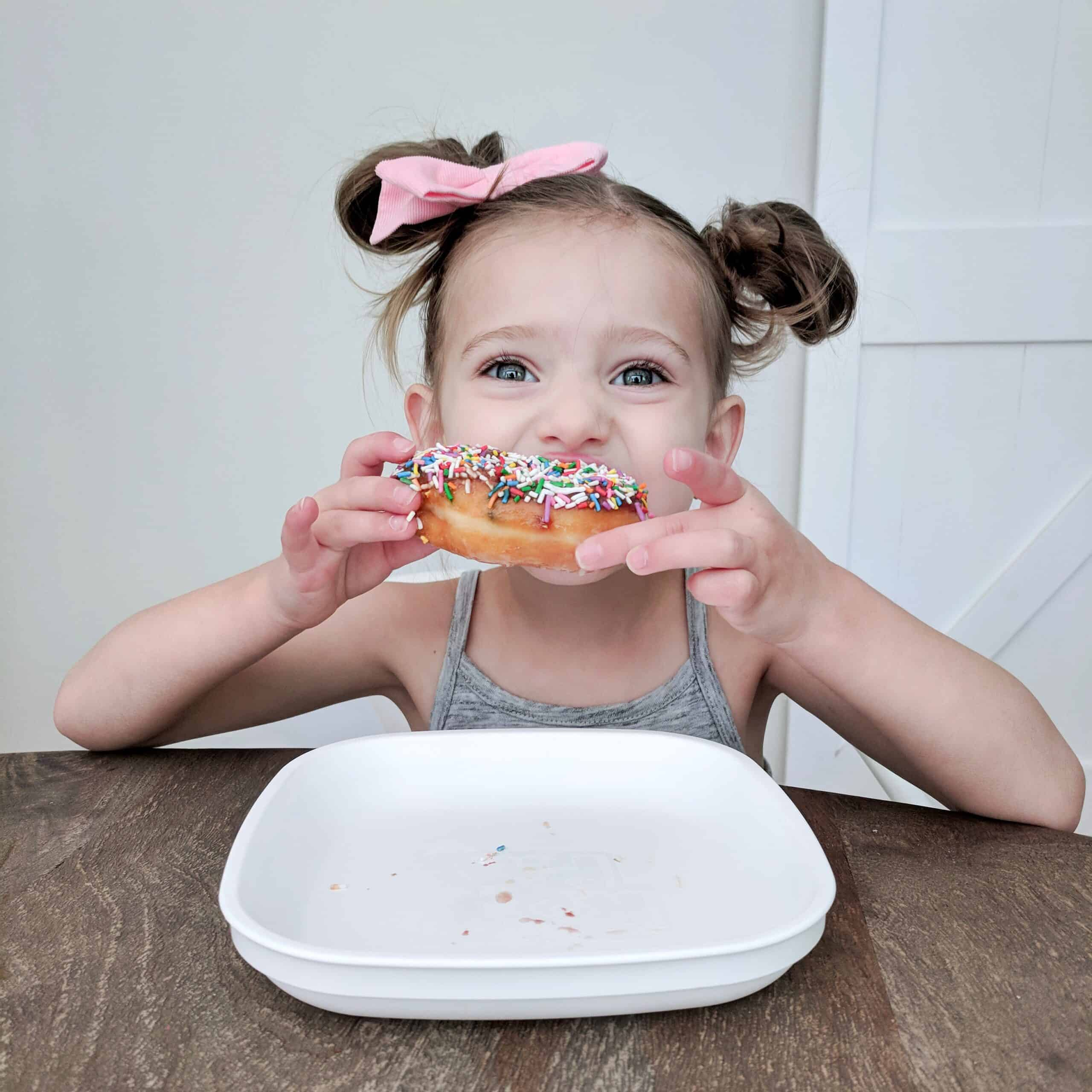 little girl eating a donut