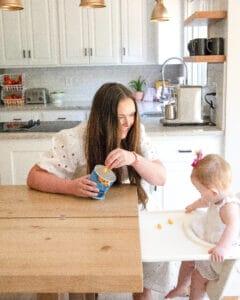 mom feeding baby Gerber Puffs