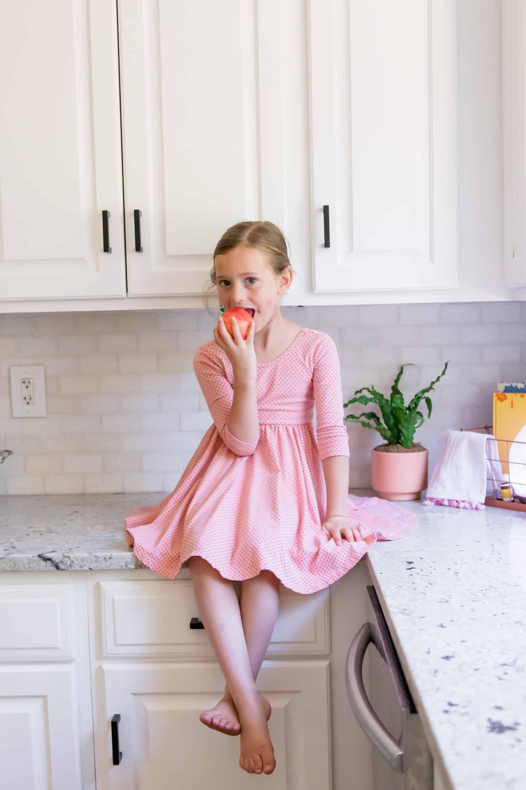 toddler girl eating apple in white kitchen