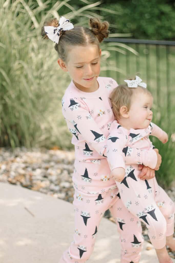 sisters in pink halloween pajamas
