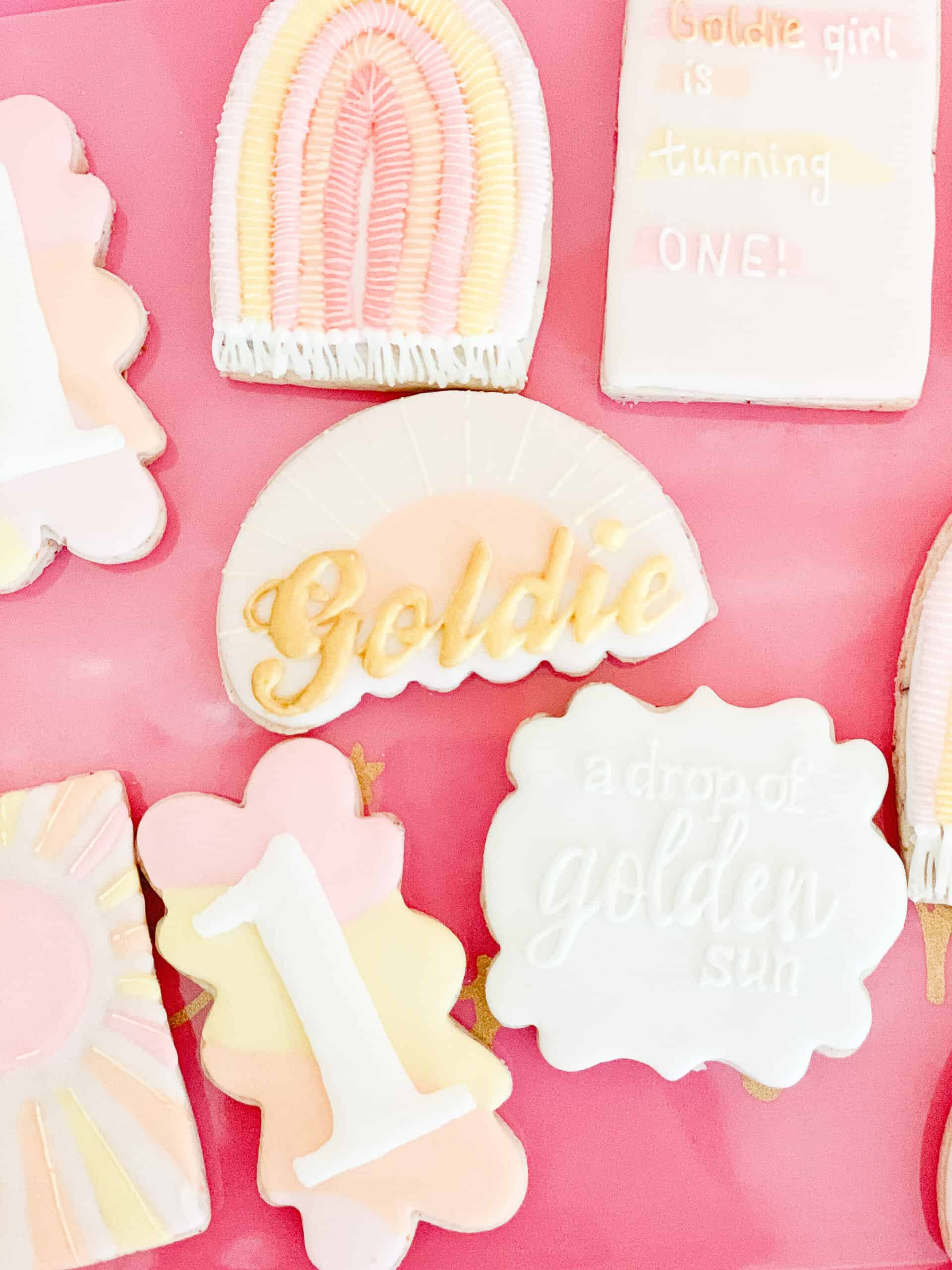 pink yellow and white birthday cookies with sunshines and rainbows