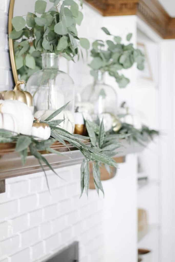 fall mantle decor that is white pumpkins and greenery