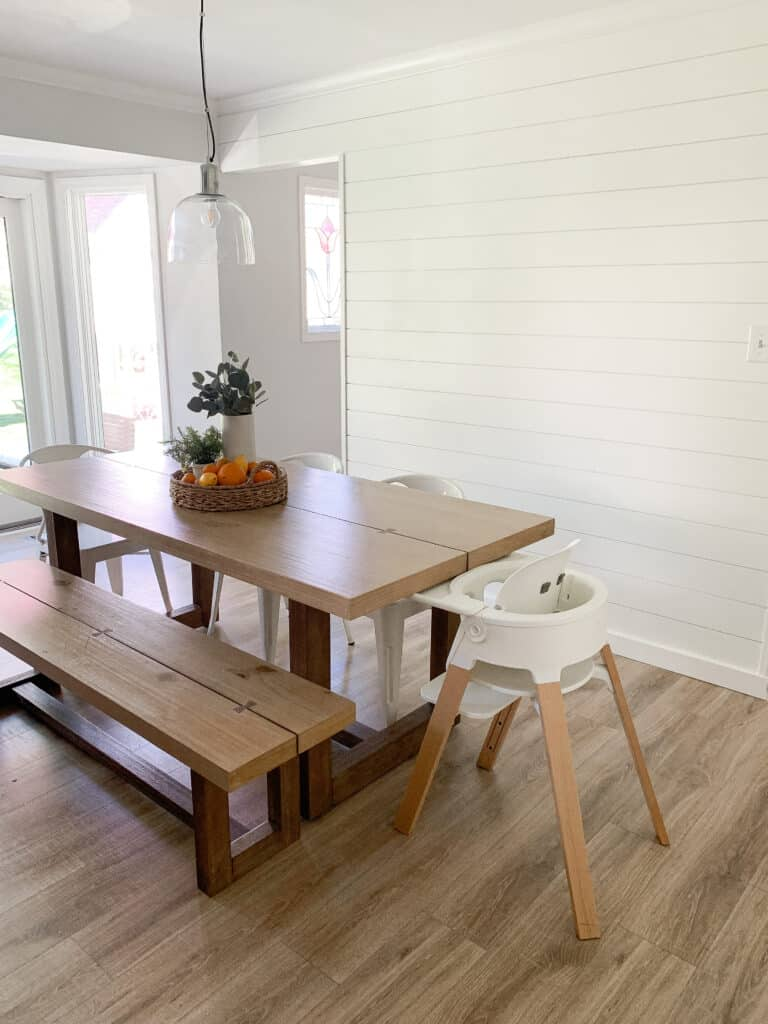 kitchen with shiplap wall and stokke highchair