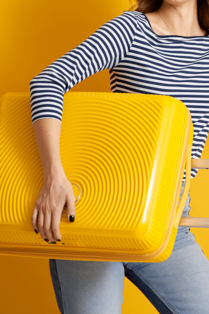 woman carrying yellow suitcase