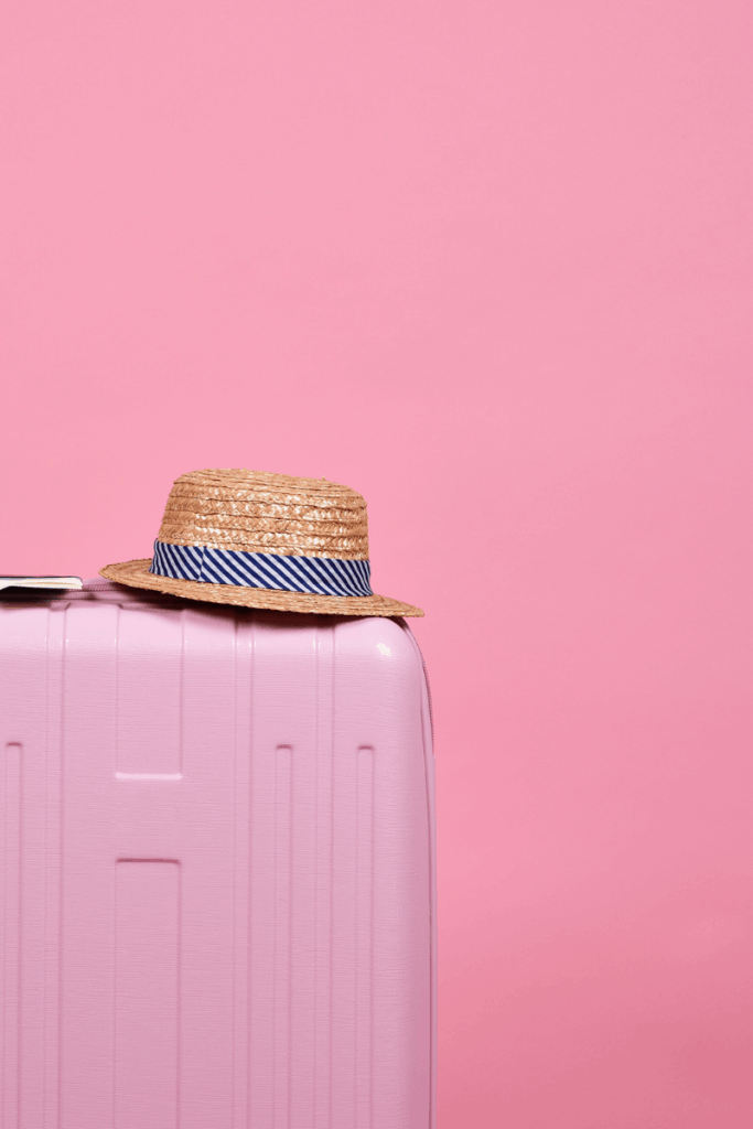 pink suitcase with hat on pink backdrop