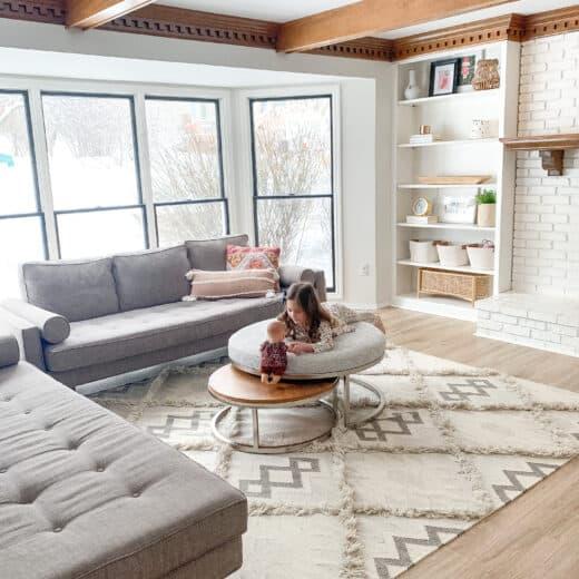 little girl on ottoman at house