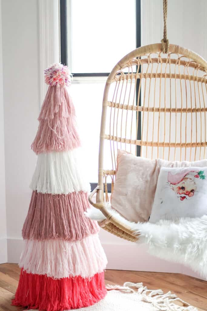 DIY Pink yarn Christmas tree  next to Serena and lily chair
