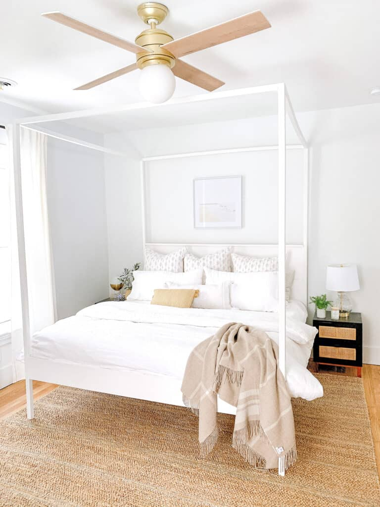 master bedroom with white bedding and white canopy bed