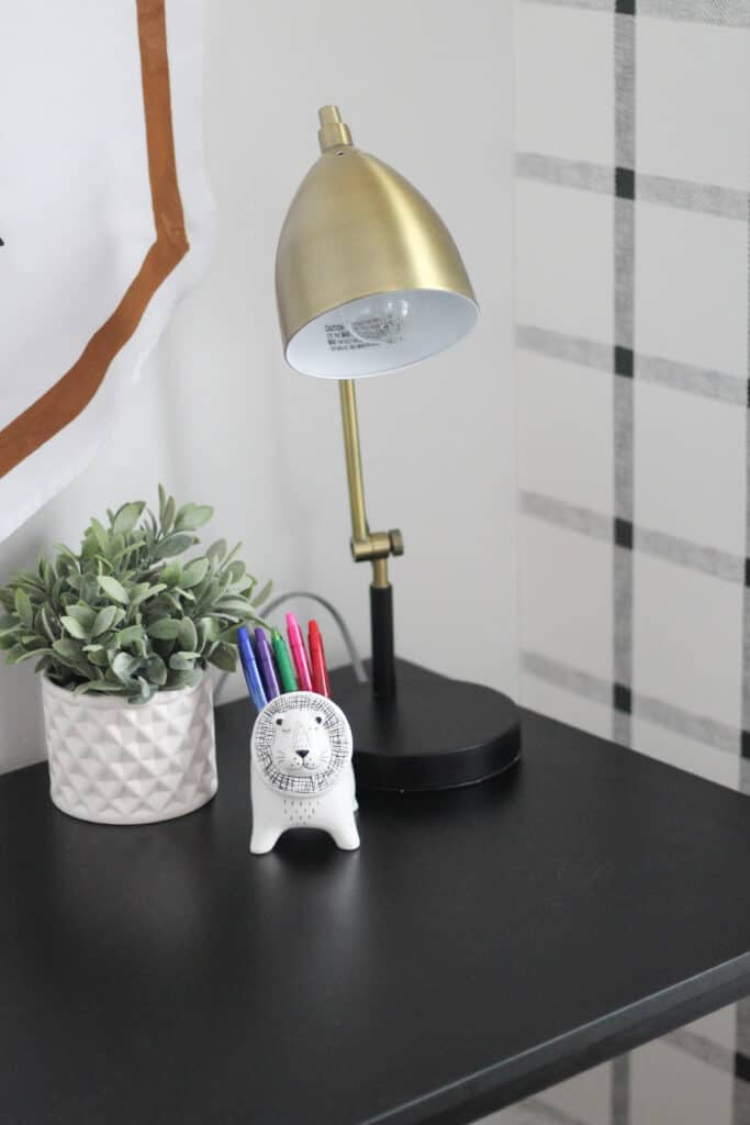desk with pens and in animal cup and gold lamp