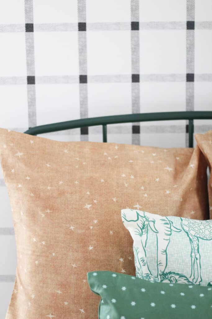 black and white plaid wallpaper with green animal pillow