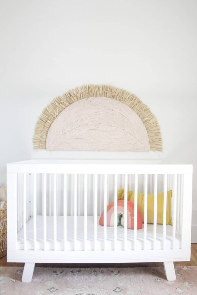 white crib with large wall hanging sunshine over