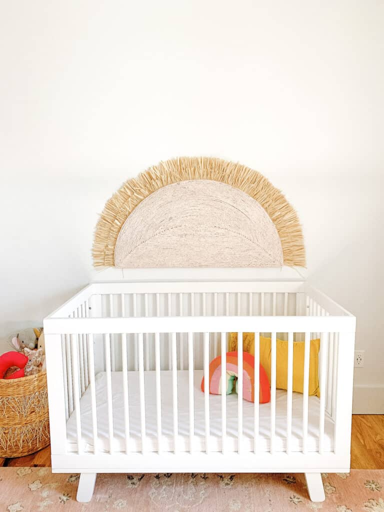 crib with large sunshine over it