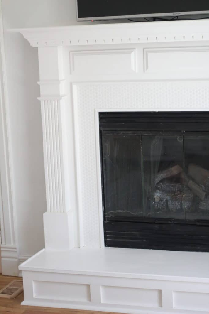 penny tile fireplace that is white with tv over it